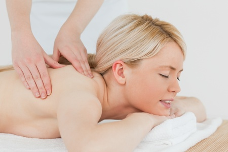 Closeup of young attractive blonde woman receiving a back massage in a spa centre photo