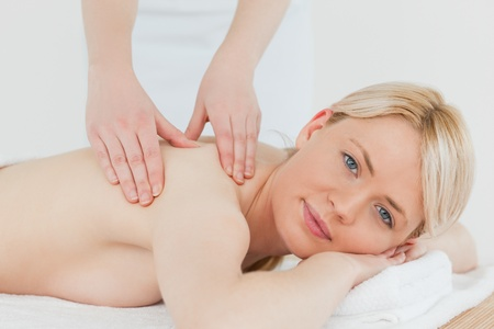 Closeup of young beautiful blonde female receiving a back massage in a spa centre photo