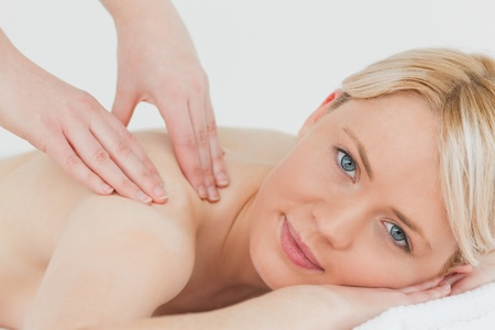 Closeup of young pretty blonde woman receiving a back massage in a spa centre photo
