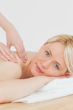 Closeup of young pretty blonde female receiving a back massage in a spa centre photo