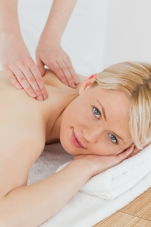 Closeup of young cute blonde female receiving a back massage in a spa centre photo
