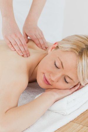 Closeup of young attractive woman receiving a back massage in a spa centre photo