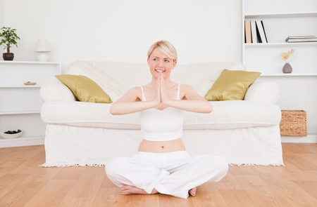 Attractive blond-haired woman practicing yoga at home photo