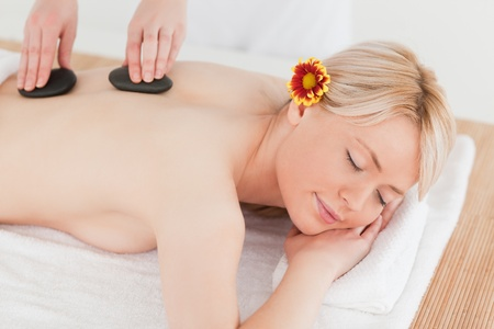 Delighted blonde woman receiving a massage with hot stones in a Spa centre photo