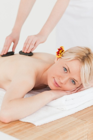 Blonde woman receiving a massage with hot stones in a Spa centre photo
