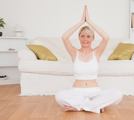 Delighted blond-haired woman practicing yoga at home photo