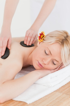 Beautiful woman receiving a massage with hot stones in a Spa centre photo