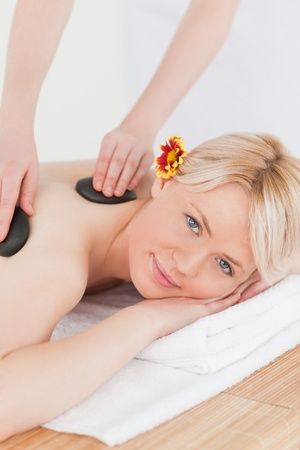 Attractive woman receiving a massage with hot stones in a Spa centre photo