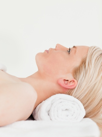 Releaxed blonde woman enjoying her treatment while lying down in a Spa centre photo