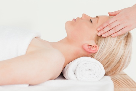 Pretty blonde woman enjoying her treatment while lying down in a Spa centre photo