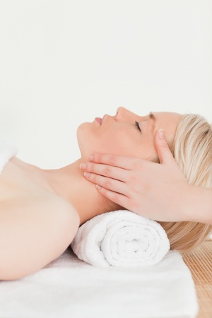 Cute blonde woman enjoying her treatment while lying down in a Spa centre photo