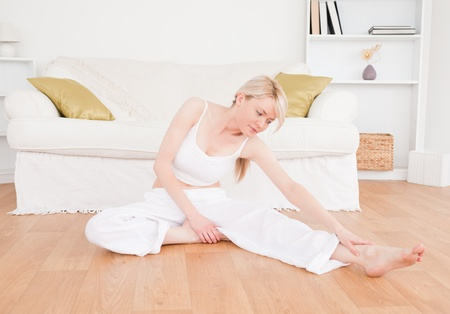 Relaxed woman doing fitness exercises in the living-room photo