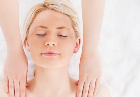 Young blond-haired woman having a massage in a Spa centre photo