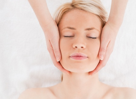 Relaxed blond-haired woman getting a massage on her face in a Spa centre photo