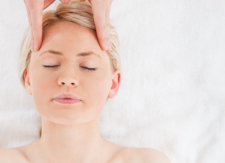 Young blond-haired woman getting a massage on her face in a Spa centre photo