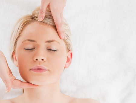 Beautiful blond-haired woman getting a massage on her face in a Spa centre photo