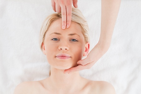 Cute blond-haired woman getting a massage on her face in a Spa centre photo