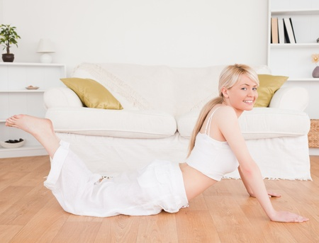 Young blond-haired woman doing fitness exercises in the living-room Stock Photo - 10194847