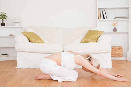 Delighted blond-haired woman doing fitness exercises in the living-room photo