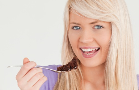 Portrait of a good looking blonde woman eating cake in the kitchen photo