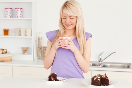 Attractive blonde woman eating cake and drinking coffee in the kitchen photo