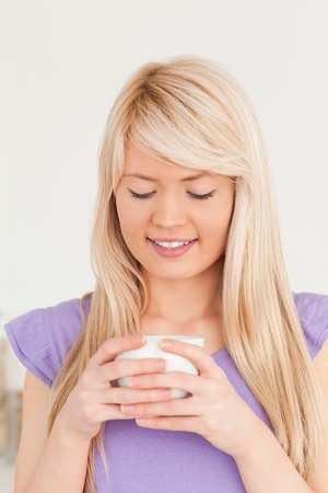 Beautiful woman drinking hot drink in the kitchen photo