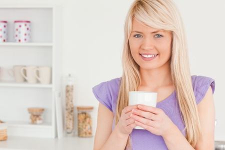 Gorgeous woman drinking hot drink in the kitchen photo