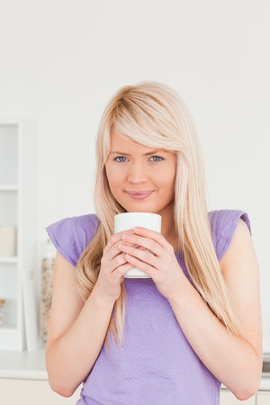 Attractive blonde female drinking hot drink in the kitchen photo