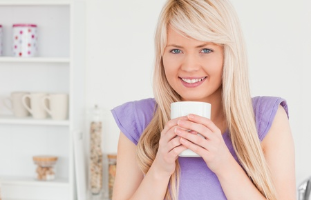 Gorgeous blonde woman drinking hot drink in the kitchen photo
