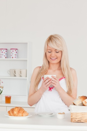 Beautiful blonde female having her breakfast in the kitchen in her appartment photo