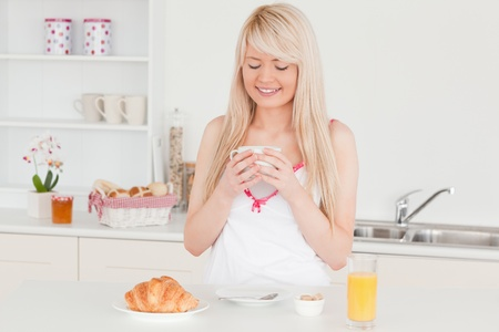 Gorgeous blonde woman having her breakfast in the kitchen in her appartment photo
