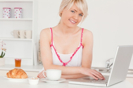 Beautiful woman having her breakfast while relaxing with a laptop in the kitchen photo