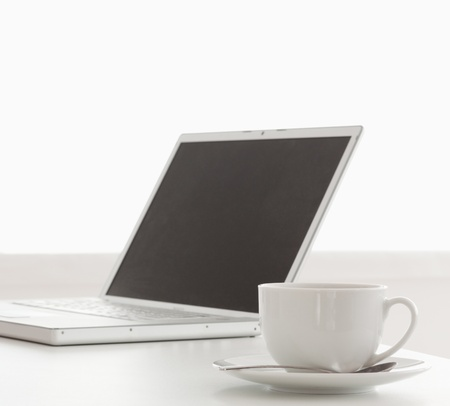Modern laptop and cup of tea on a table in the kitchen Stock Photo - 10194099