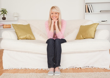 Beautiful blonde woman posing while sitting on a sofa in the living room Stock Photo - 10198291