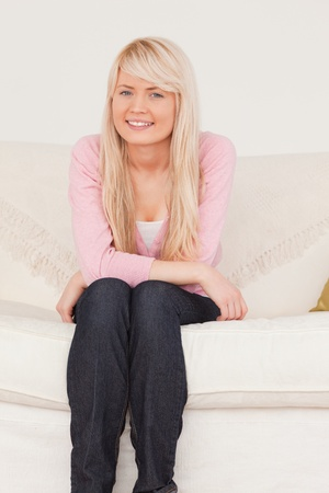 Attractive blonde female posing while sitting on a sofa in the living room photo