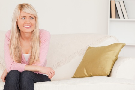 Good looking blonde woman posing while sitting on a sofa in the living room Stock Photo - 10206040