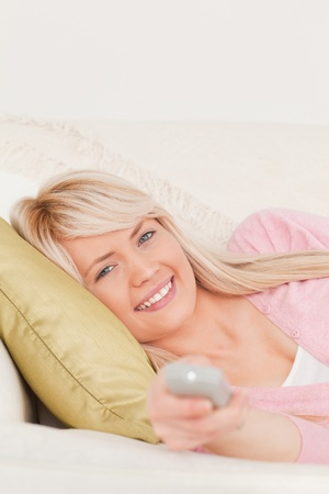 Beautiful blonde female posing while lying on a sofa in the living room Stock Photo - 10198861