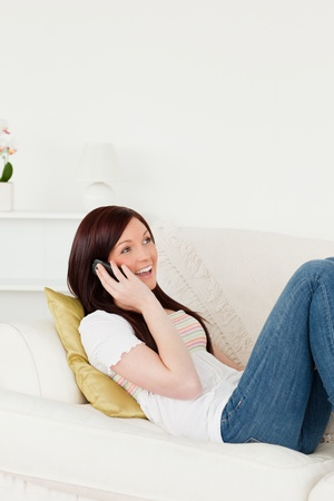 Pretty red-haired woman having a conversation on the phone while lying on a sofa in the living room photo
