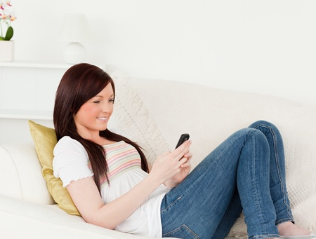 Beautiful red-haired woman writing a text on her phone while lying on a sofa in the living room photo