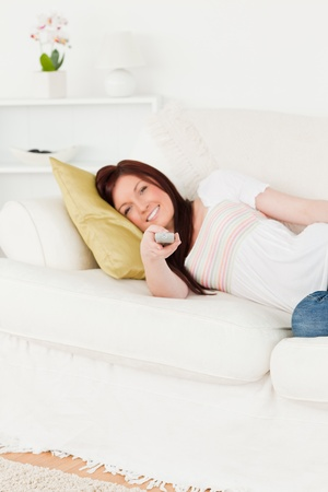 Cute red-haired woman watching tv while lying on a sofa in the living room photo