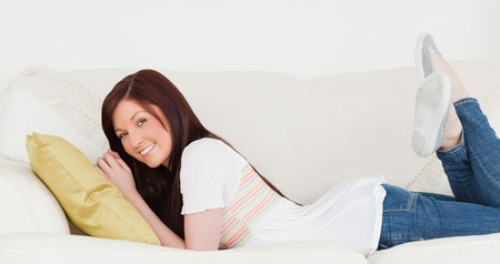 Attractive red-haired woman posing while lying on a sofa in the living room Stock Photo - 10197609