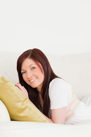 Beautiful red-haired woman posing while lying on a sofa in the living room Stock Photo - 10197558