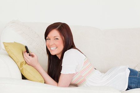 Attractive red-haired female writing a text on her phone while lying on a sofa in the living room photo