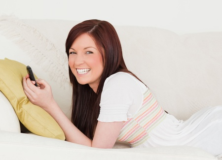 Good looking red-haired female writing a text on her phone while lying on a sofa in the living room photo