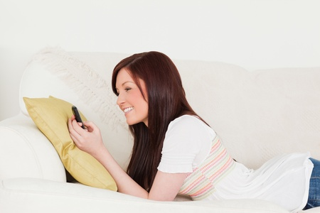 Beautiful red-haired female writing a text on her phone while lying on a sofa in the living room photo
