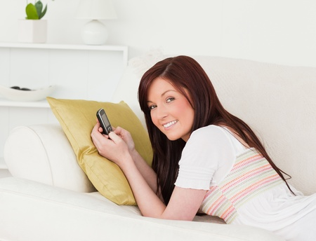 Joyful red-haired female writing a text on her phone while lying on a sofa in the living room photo
