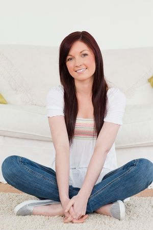 Smiling red-haired woman posing while sitting on a carpet in the living room photo