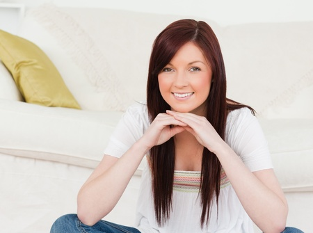 Good looking red-haired woman posing while sitting on a carpet in the living room Stock Photo - 10196016