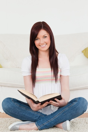 Beautiful red-haired woman reading a book while sitting on a sofa in the living room photo