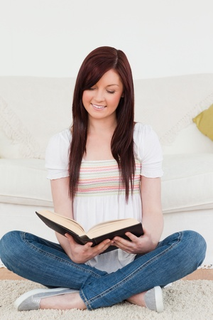 Attractive red-haired woman reading a book while sitting on a sofa in the living room photo